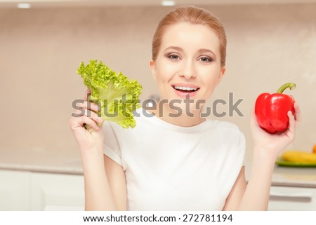 Happiness in hands. Smiling woman holding lettuce in one hand and peper in another hand looking at you