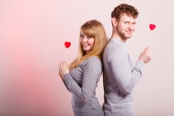 Happiness in love. Lovely charming couple smiling. Happy joyful woman and man holding little hearts on sticks. Two people with sign symbol of good relationship feelings.