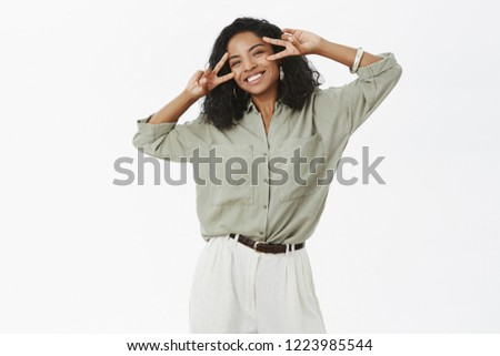 Happiness is near. Portrait of carefree charming and upbeat young african american sucessful female in blouse and pants with tattoo showing peace signs over eyes and smiling joyfully