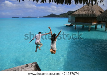 Happiness jump of young couple on the water. Over water bungalows at Bora Bora, French Polynesia.