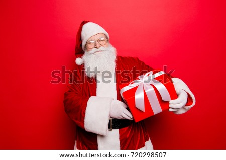 Happiness, noel, festive seosonal occasion. Funny Saint Nicholas in red traditional fur coat and head wear with a wrapped gift with bow, isolated on red background, wishing holly jolly x mas #720298507