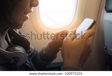 Happiness of Asian girl with headphone using smartphone and smiling on the airplane.