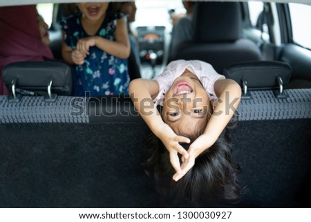 happiness of daughter lean back on seat back the car, look back to the baggage with somersault position #1300030927