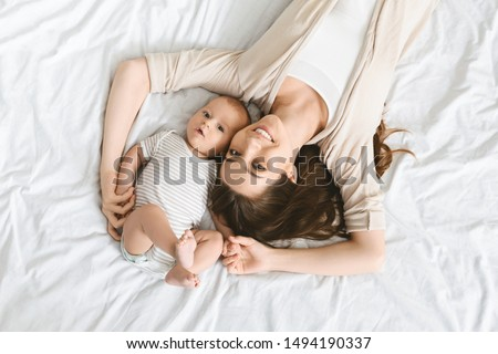 Happiness of motherhood. Smiling mother and her cute little infant baby lying on bed, top view