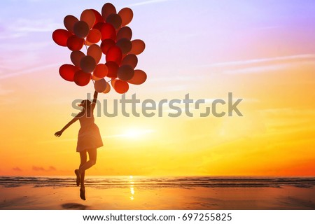 happiness or dream concept, silhouette of happy woman jumping with multicolored balloons at sunset on the beach #697255825