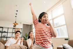 happiness pleasure asian lovely family enjoy watch and cheer up little daughter girl singing and dance practice in front of tv in living room