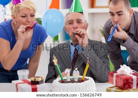 Happiness senior man celebrating 70th birthday with family