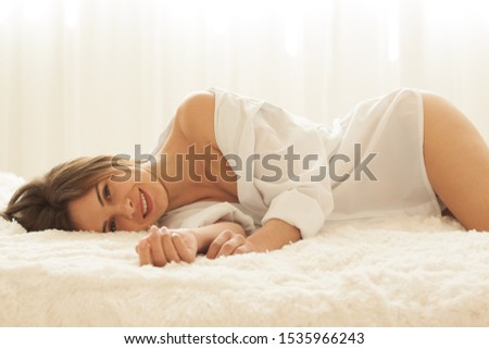Happiness sensual young woman in a white man's shirt relaxing on a bed