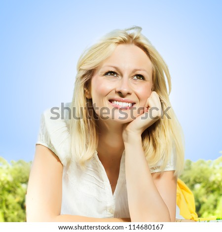 Happiness smiling blonde woman relaxing on green grass in the park, against clear blue sky .