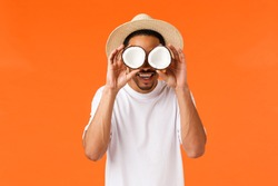 Happiness, vacation and tourism concept. Funny carefree african-american guy in white t-shirt, summer hat, holding coconuts on eyes and smiling amused, fooling around, standing orange background