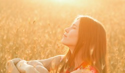 Happiness woman stay outdoor under sunlight of sunset.Beauty Romantic Girl Outdoors. Beautiful Teenage Model girl in Casual Short Dress on the Field in Sun Light. Blowing Long Hair. Autumn. Glow Sun,
