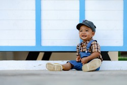 Happiness 1 year old cute toddler Asia boy kid in bib jeans sitting and smilling in front of white wall background with copy space.