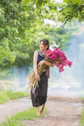 Happy A beautiful thai woman with pink lotus in hand walking on the road