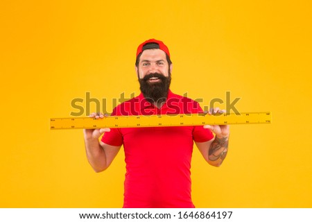 happy about size. Bearded man with big measuring instrument. Measuring his height with ruler. gauge and measuring. university student hold ruler. size measurement. school disciplines. back to school.