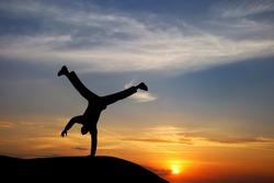 Happy acrobat man at the sunset.Emotional scene.