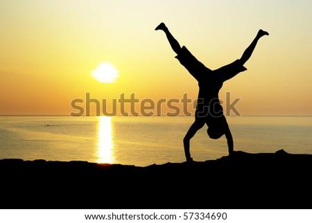 Happy acrobat on the sunset. Emotional scene.