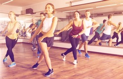 Happy active adult men and ladies dancing zumba at lesson