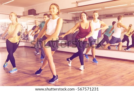 Happy active adult men and ladies dancing zumba at lesson #567571231