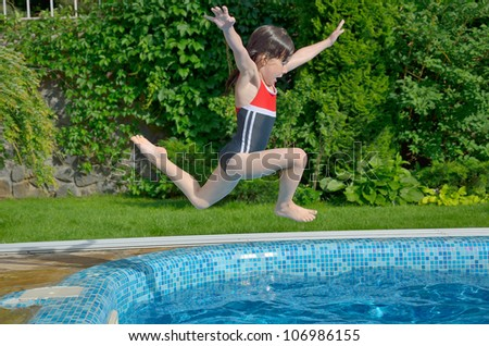 Happy Active Child Jumps To Swimming Pool Beautiful Smiling Girl Having Fun On Summer Vacation