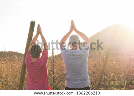 Happy active couple of old senior cacuasian people man and woman do yoga position for healthy lifestyle outdoor leisure activity - sunlight in backlight during sunset in country side #1362206210