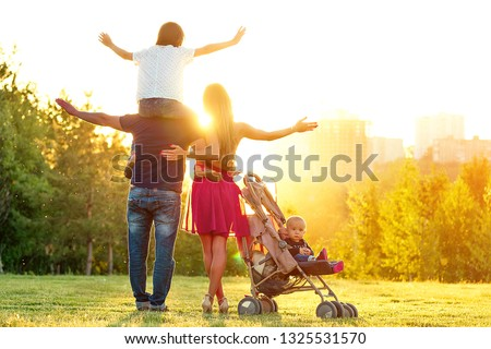 Happy active family photosession in the summer park. beautiful long-haired mother her husband with her daughter and son in a stroller rest on the nature green lawn . concept of freedom back view #1325531570
