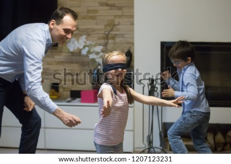 Happy active family spends time together on weekend at home. Single father and little preschool children playing enjoy game hide and seek. Small blind girl with covered eyes catching daddy and brother