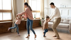 Happy active family young mom dad and cute little children daughters holding hands dancing together in living room interior, carefree funny small kids having fun jumping laughing with parents at home