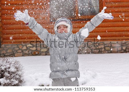 Happy active girl having fun and throwing snow in winter forest, smiling playing child. Kid on winter vacation - stock photo
