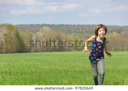 Happy active girl running on green field. Child and nature in spring, summer