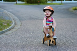Happy active little kid, beautiful blonde toddler girl in colorful dress and safety helmet playing outdoors on the street riding her push bike, wooden horse with three wheels, on a sunny summer day