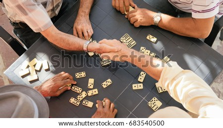 Happy active retired people, old hispanic senior men having fun and playing game of domino at home. Buddies celebrating victory and cheering
