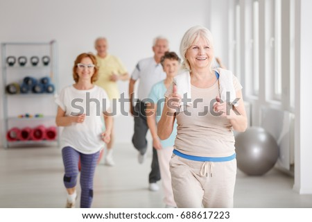 Happy active seniors exercising together in white spacious room #688617223