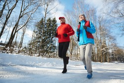 Happy active seniors in sportswear jogging down winter road in natural environment