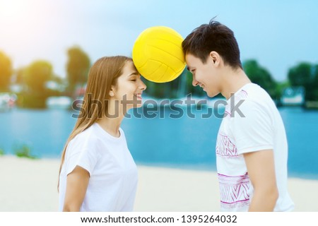 Happy active smiling romantic couple keep the ball heads game on sand beech with blue river lake sky with clouds behind Concept of spring summer outdoor amusement activities entertainment sport trust  #1395264032