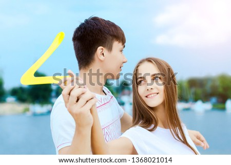 Happy active smiling romantic couple playing boomerang Girl swings game on sand beech with blue river lake sky with clouds behind Concept of spring summer outdoor amusement activities entertainment #1368021014