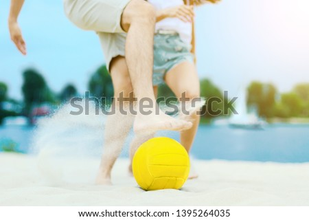 Happy active smiling romantic couple playing football game on sand beech with blue river lake sky with clouds behind Concept of spring summer outdoor amusement activities entertainment sport leisure  #1395264035