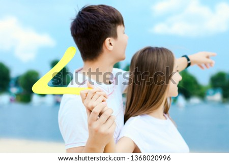 Happy active smiling romantic couple playing swings boomerang game on sand beech with blue river lake sea sky with clouds behind Concept of spring summer outdoor amusement activities entertainment #1368020996