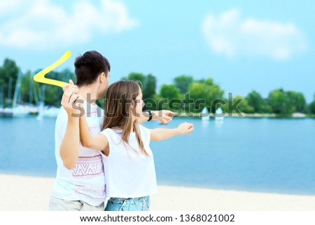 Happy active smiling romantic couple playing swings boomerang game on sand beech with blue river lake sea sky with clouds behind Concept of spring summer outdoor amusement activities entertainment #1368021002