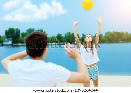 Happy active smiling romantic couple playing volleyball girl hit ball game on sand beech with blue river lake sky with clouds behind Concept of spring summer outdoor amusement activities entertainment
