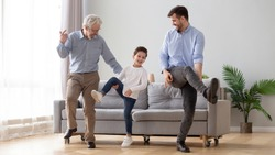 Happy active 3 three generation men family senior old grandfather, young adult dad and cute little kid son grandson dancing having fun playing together enjoy leisure lifestyle in living room at home