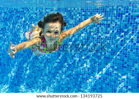 Happy active underwater child swims in pool, beautiful healthy girl swimming and having fun on family summer vacation, kids sport concept