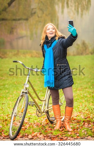 Happy active woman with bike bicycle in fall autumn park taking selfie self photo picture. Glad young girl in jacket and scarf relaxing. Healthy lifestyle.