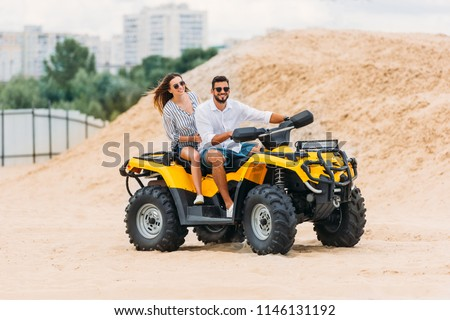 happy active young couple riding all-terrain vehicle in desert Stock photo ©
