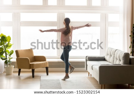 Happy active young woman dancing alone in modern living room interior with big window enjoying cozy weekend lifestyle, joyful carefree millennial girl listening music having fun at home apartment Stockfoto ©