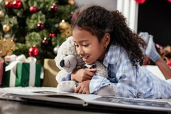 happy adorable african american child in pajamas with teddy bear looking at photo album on floor at home
