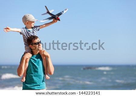 happy adorable boy holding toy plane and sitting on his young handsome father shoulders and having fun together outdoors