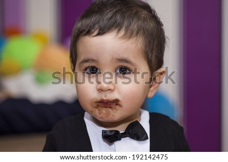 Happy, Adorable happy baby eating chocolate, wearing suit and bow tie