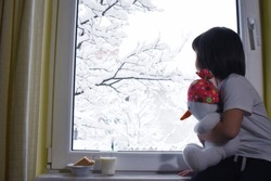 Happy adorable kid boy sitting near window and fascinated looking outside on snowfall on Christmas day. Child eat cookies and drink milk near window. Child hugging toy Snowman in front of window