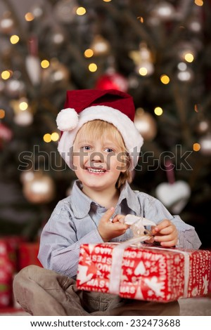 Happy adorable small boy opening an Xmas gift sitting in front of the Christmas tree with a gift-wrapped box on his lap smiling at the camera