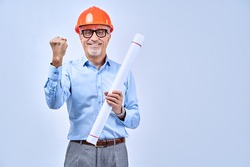Happy adult architect holding blueprints, isolated on blue background. Copy space. Construction and design concept